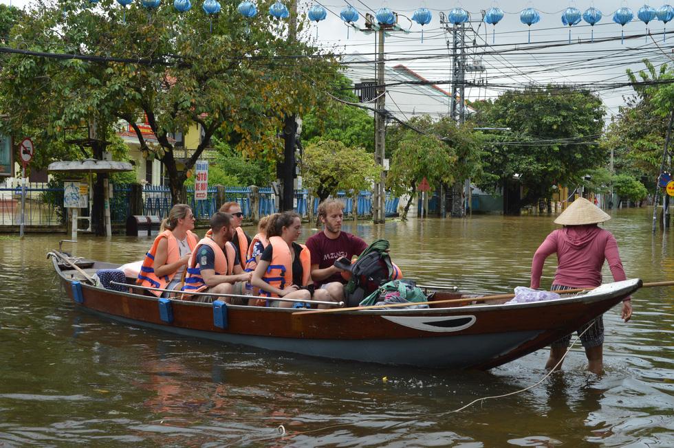 Hội An tấp nập ghe tàu đưa du khách dạo phố cổ mùa mưa lũ - Ảnh 2.