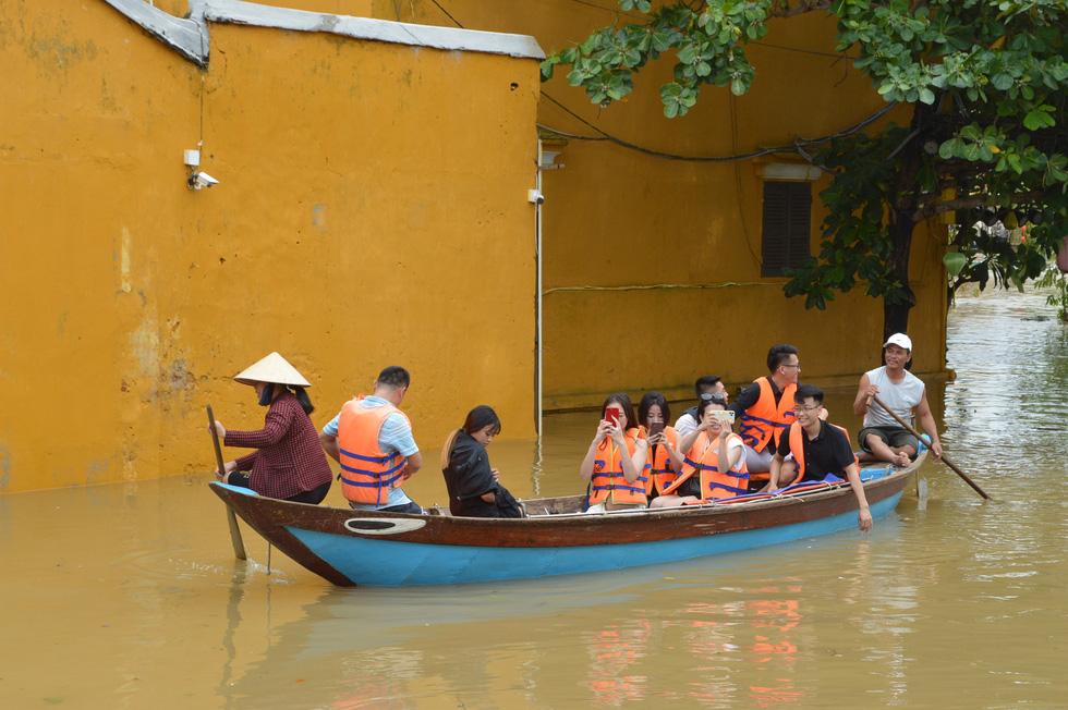 Hội An tấp nập ghe tàu đưa du khách dạo phố cổ mùa mưa lũ - Ảnh 3.