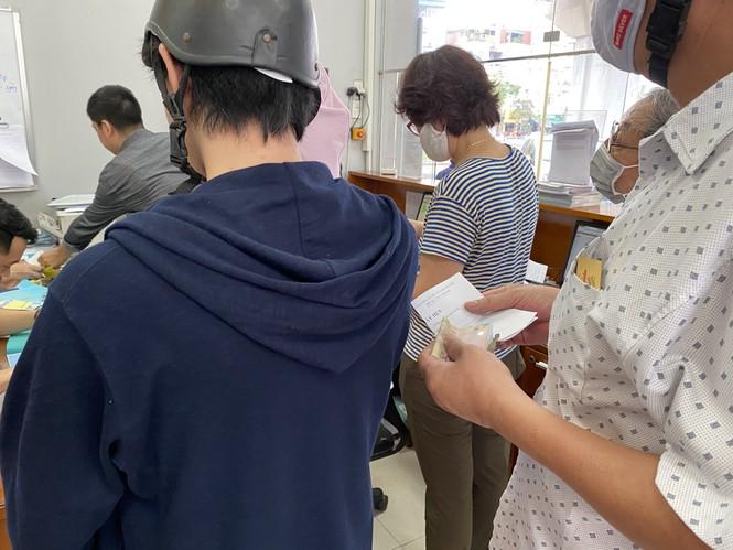 Người dân Hà Nội xếp hàng mua bảo hiểm xe máy - Ảnh 7.