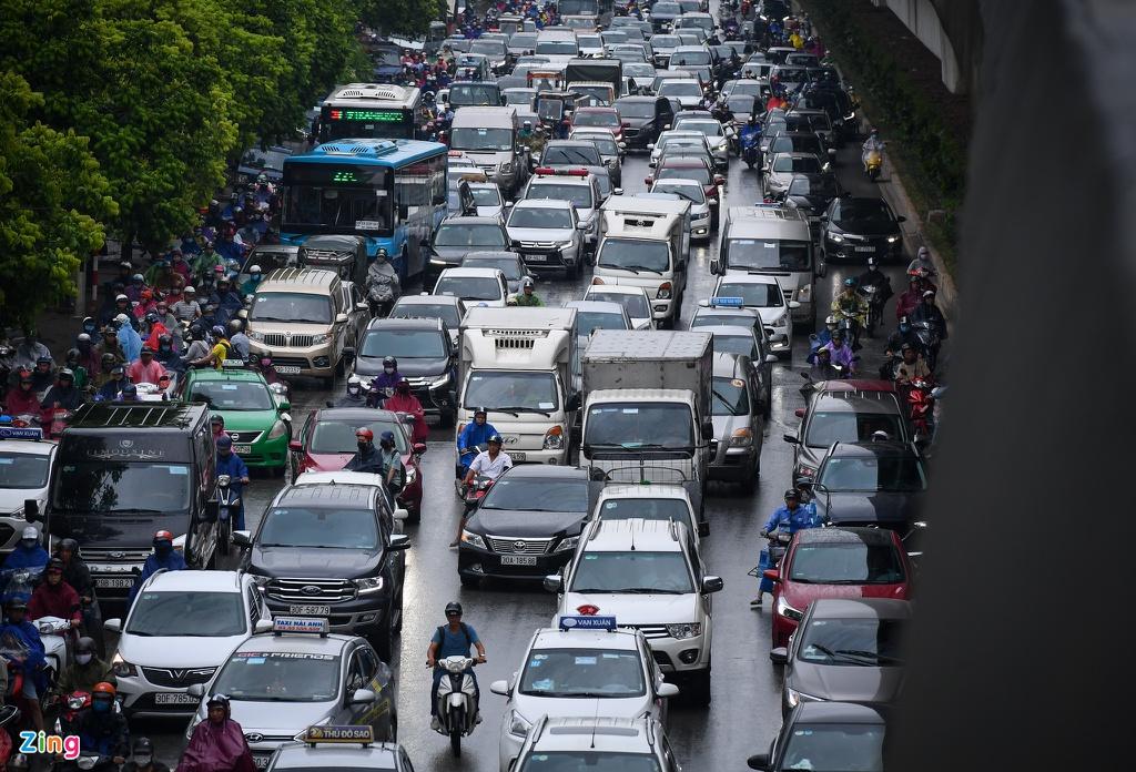 Đường phố Hà Nội rối loạn trong cơn mưa đầu tuần - Ảnh 1.
