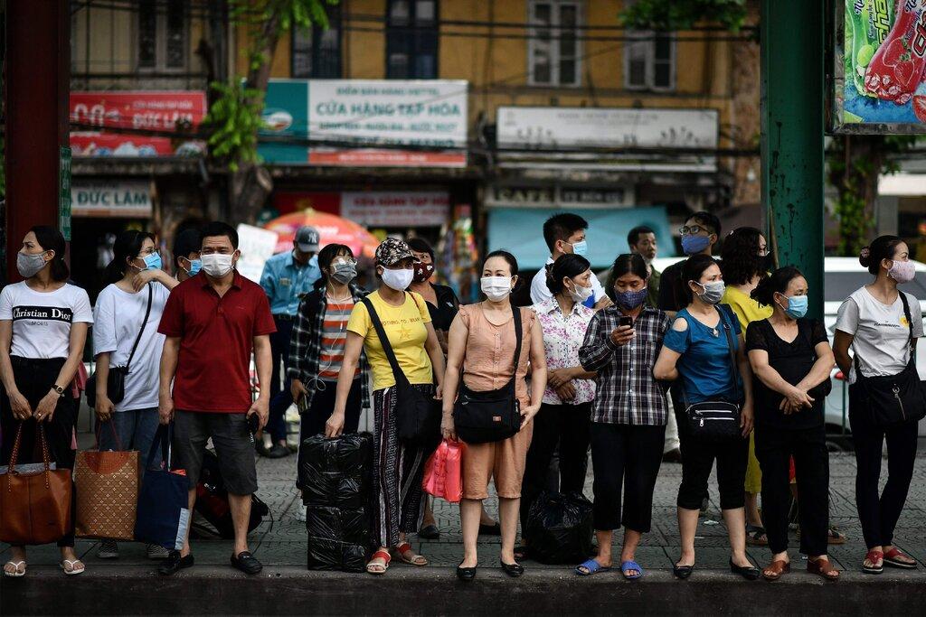 Người dân bắt đầu lại thói quen đeo khẩu trang khi ra ngoài. (Ảnh: Manan Vatsyayana / Agence France-Presse)