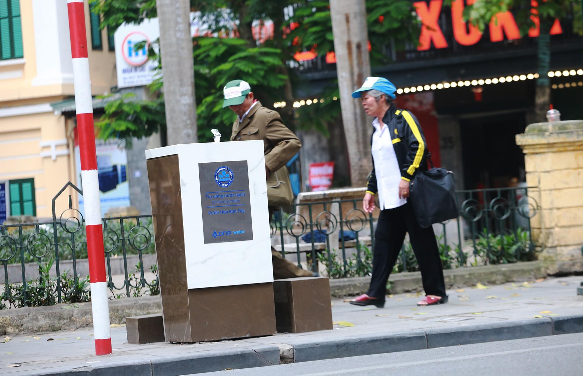 Học sinh, người lao động thích thú khi được uống nước sạch miễn phí trên đường phố Hà Nội - Ảnh 1.