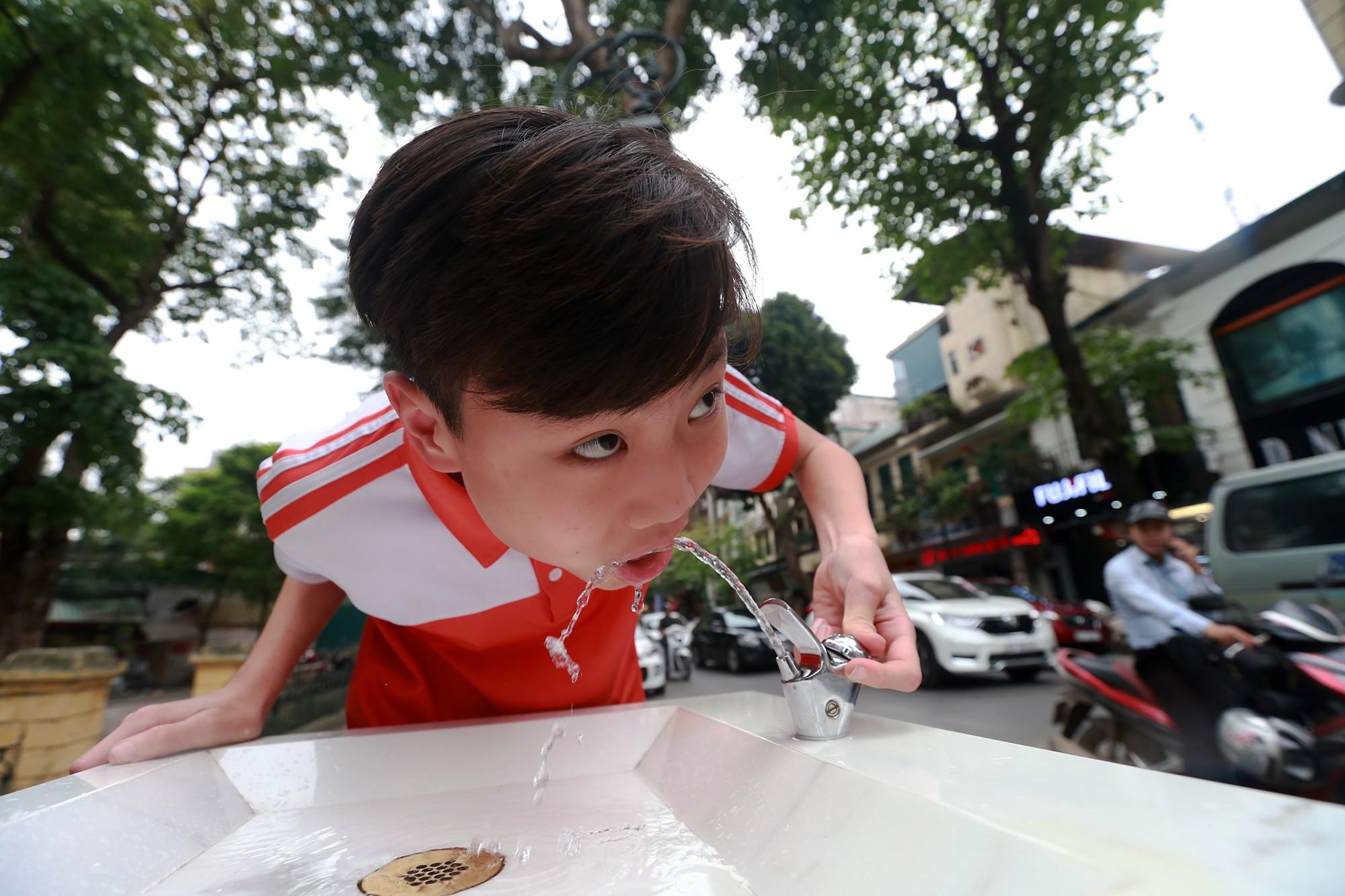 Học sinh, người lao động thích thú khi được uống nước sạch miễn phí trên đường phố Hà Nội - Ảnh 11.