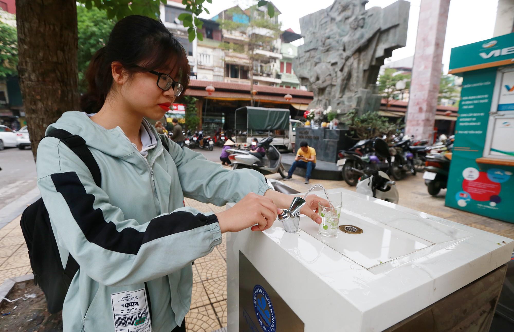 Học sinh, người lao động thích thú khi được uống nước sạch miễn phí trên đường phố Hà Nội - Ảnh 9.