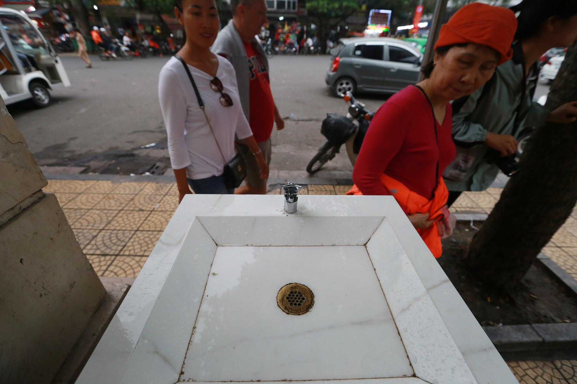 Học sinh, người lao động thích thú khi được uống nước sạch miễn phí trên đường phố Hà Nội - Ảnh 3.