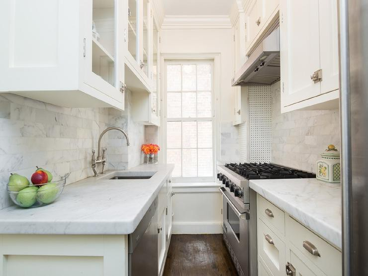 small-white-galley-kitchen-stove-facing-sink-glass-front-cabinets