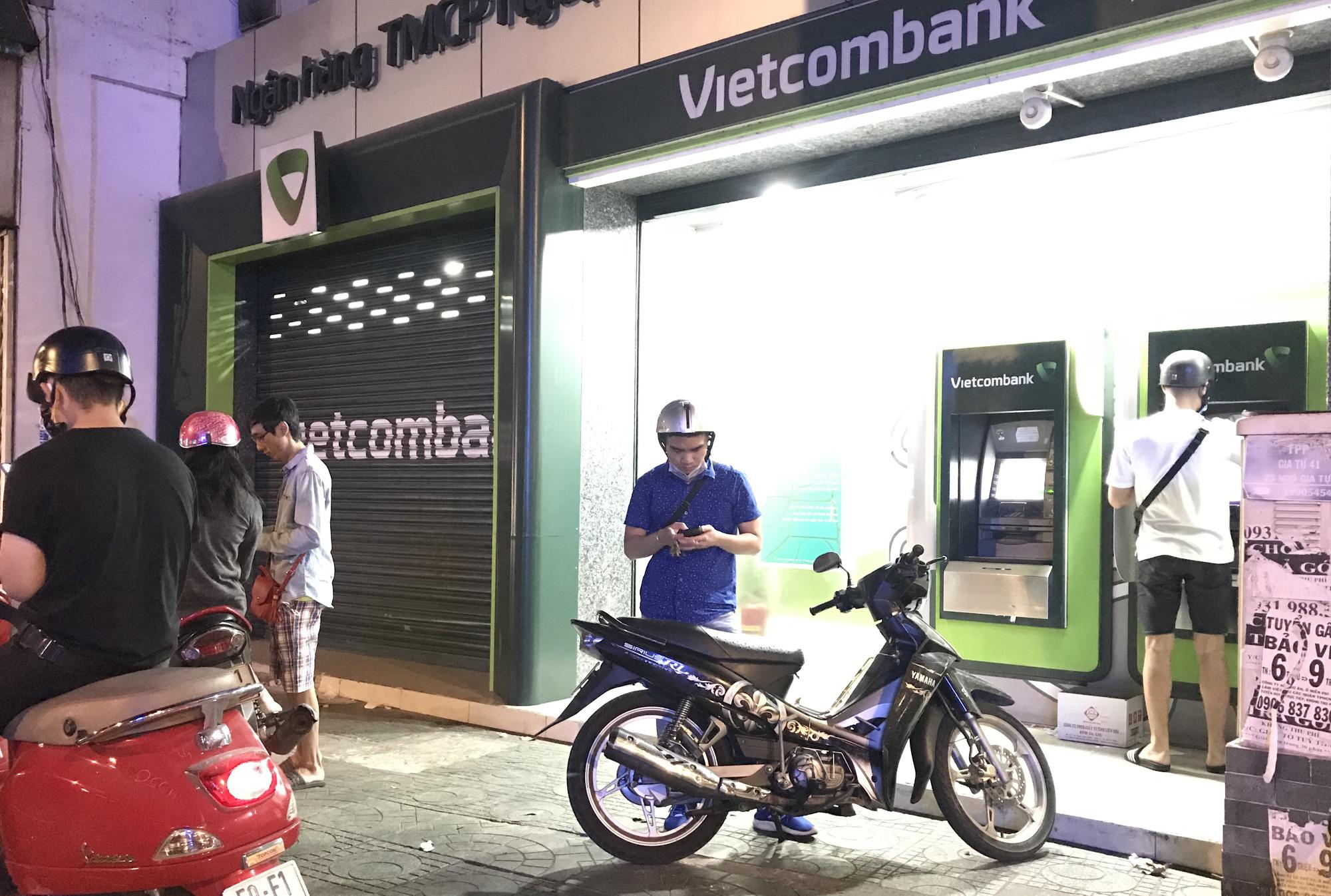 ATM tại Sài Gòn đồng loạt nghỉ Tết, chạy cả đêm vẫn không rút được tiền lương, thưởng để về quê - Ảnh 1.