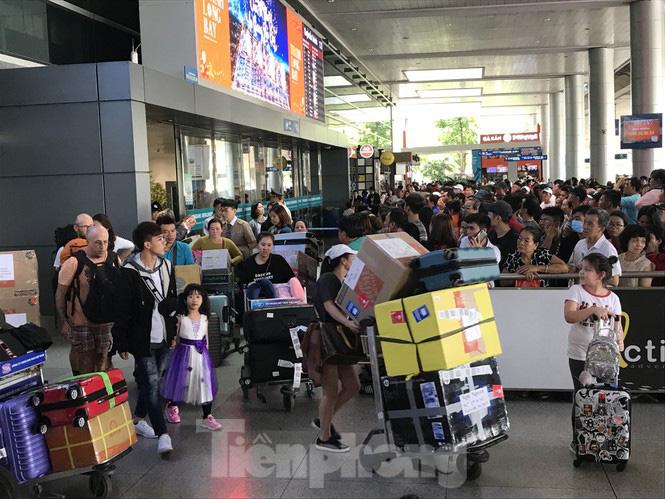 Nghìn người chen lấn ở sân bay Tân Sơn Nhất đón Việt kiều về quê ngày 29 tết - Ảnh 1.
