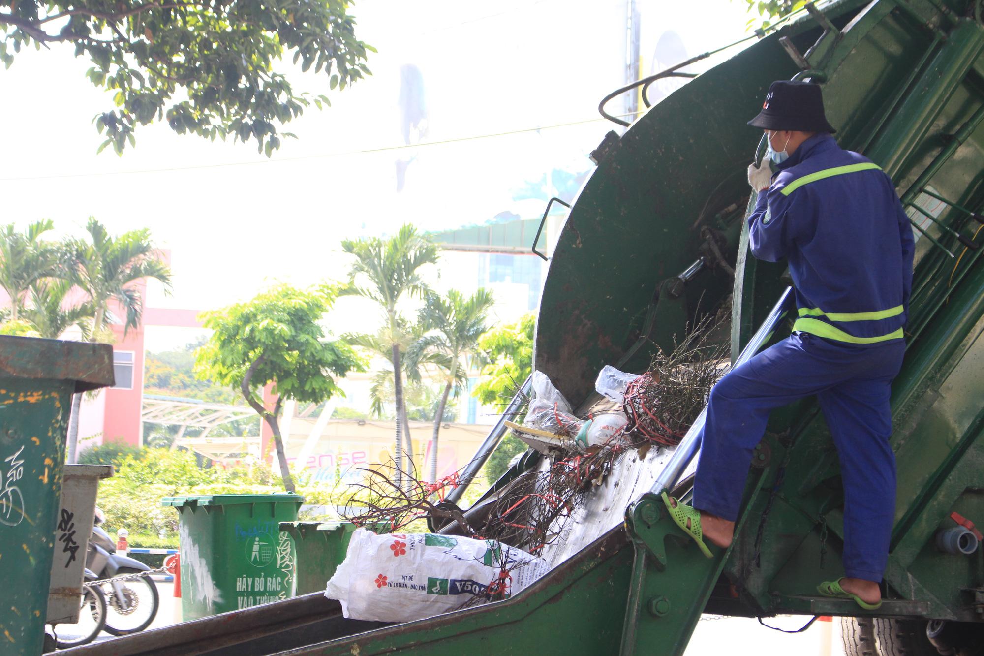 Đập nát hoa trước quăng lên xe rác ở Sài Gòn trưa 30 Tết - Ảnh 11.