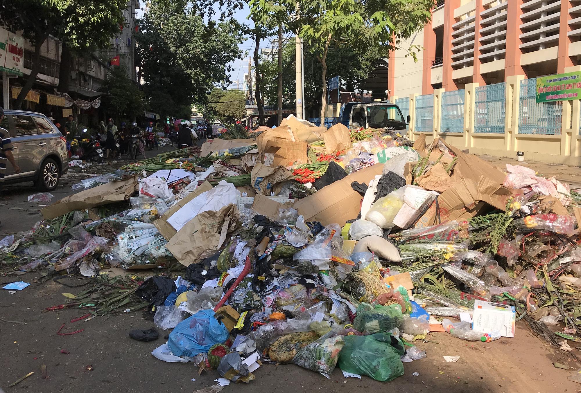 Hoa tươi tại 2 chợ hoa sỉ lớn nhất Sài Gòn chất đống lên xe rác trưa 30 Tết - Ảnh 1.