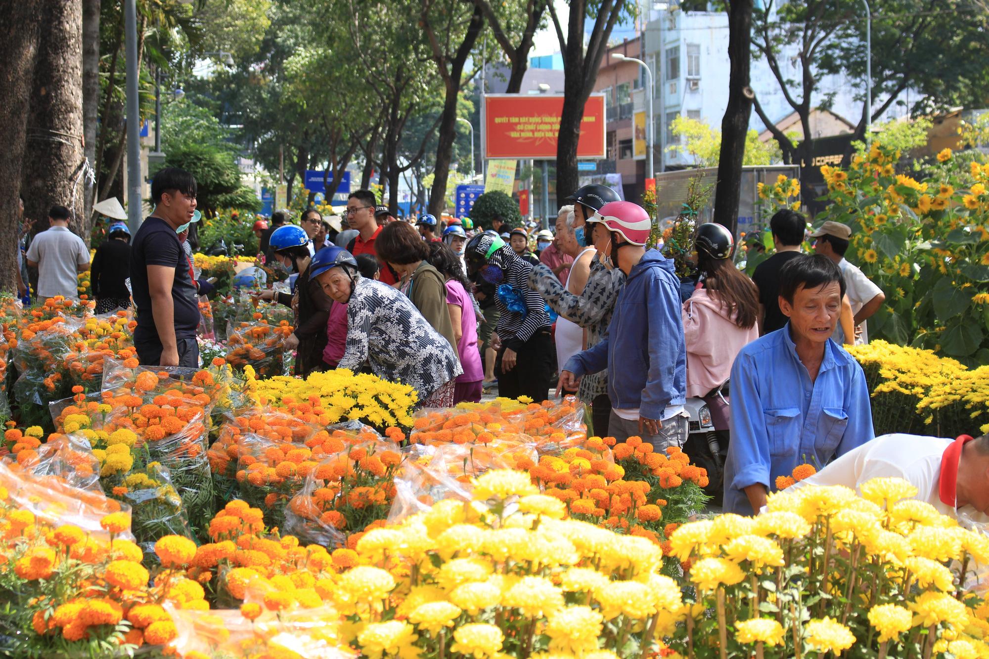 Trưa 30 Tết, mai, đào, hướng dương bán rẻ như cho 50.000 đồng một cây ở chợ hoa Sài Gòn - Ảnh 1.