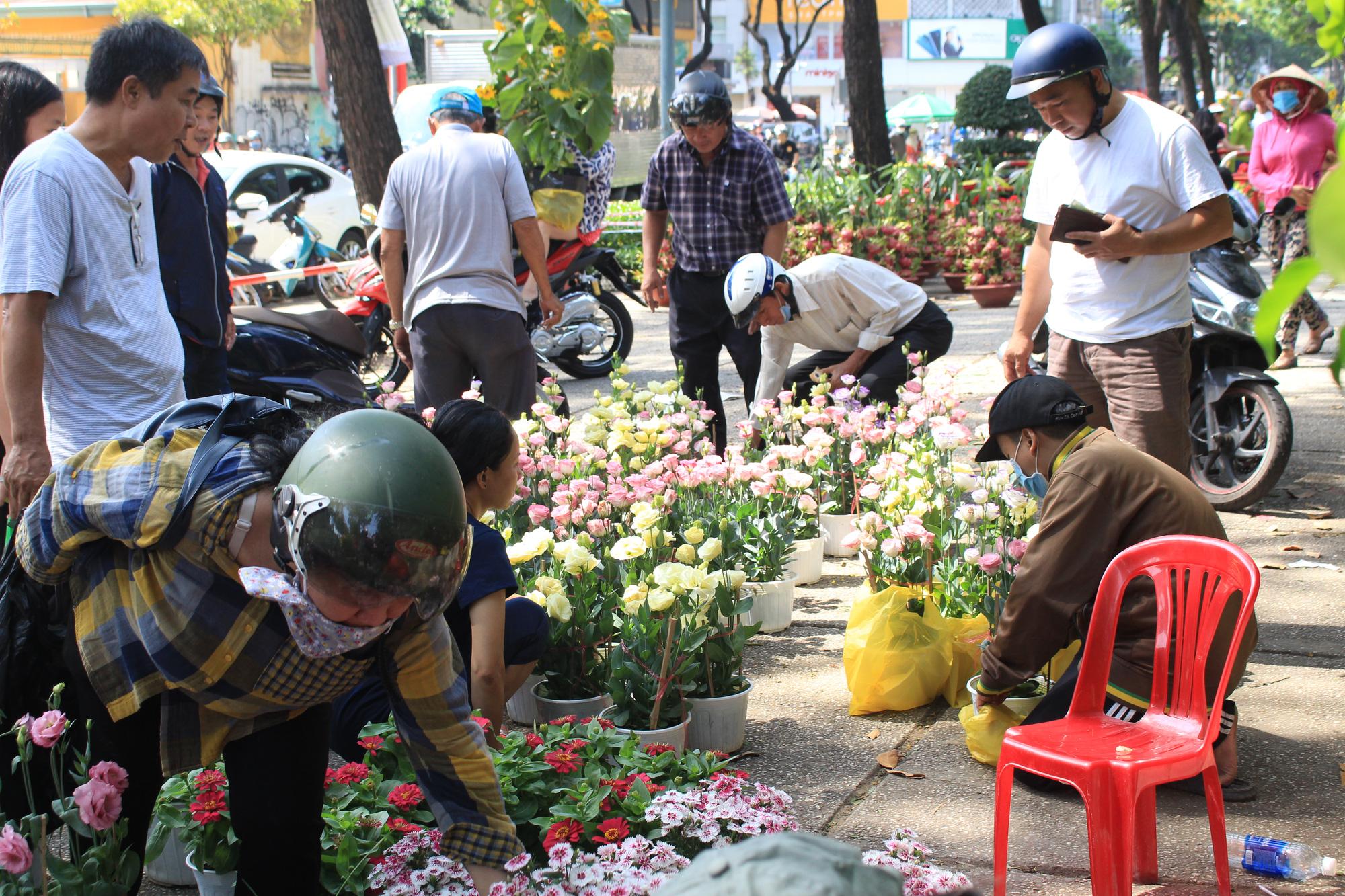 Trưa 30 Tết, mai, đào, hướng dương bán rẻ như cho 50.000 đồng một cây ở chợ hoa Sài Gòn - Ảnh 2.