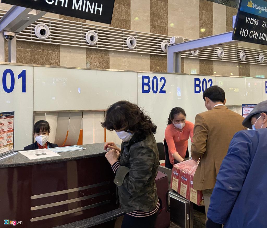 Hành khách, tiếp viên đeo khẩu trang kín mít ở sân bay ngày đầu năm - Ảnh 1.