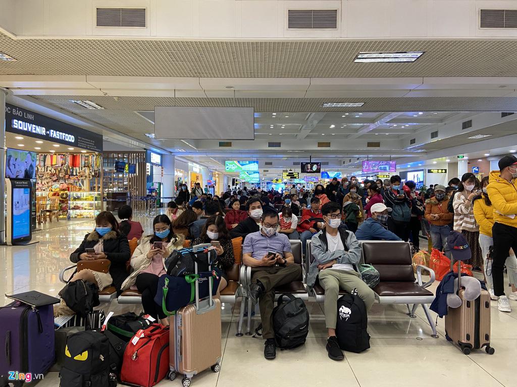 Hành khách, tiếp viên đeo khẩu trang kín mít ở sân bay ngày đầu năm - Ảnh 2.