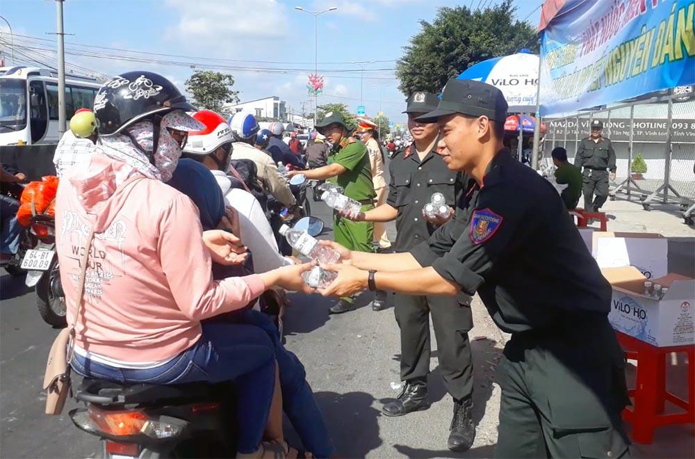 Nữ CSGT đội nắng phát nghìn chai nước suối cho người dân ngày mùng 5 Tết - Ảnh 6.