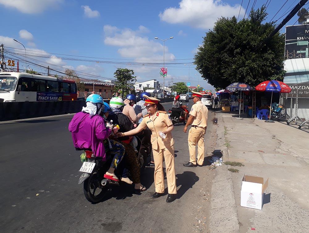 Nữ CSGT đội nắng phát nghìn chai nước suối cho người dân ngày mùng 5 Tết - Ảnh 2.