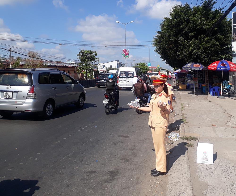 Nữ CSGT đội nắng phát nghìn chai nước suối cho người dân ngày mùng 5 Tết - Ảnh 1.