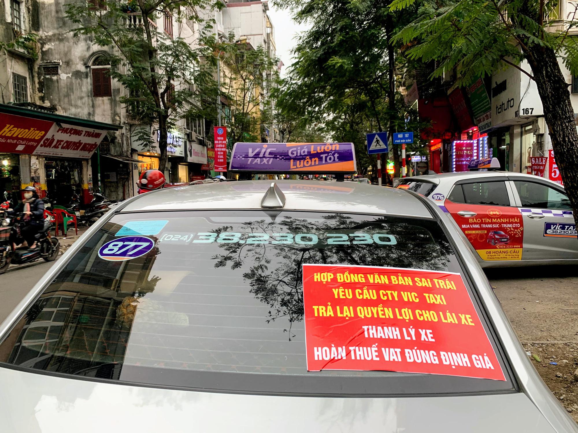 Hàng trăm tài xế Taxi Vic vây ráp trụ sở chính tại Hà Nội, căng biển 'đòi xe' - Ảnh 1.