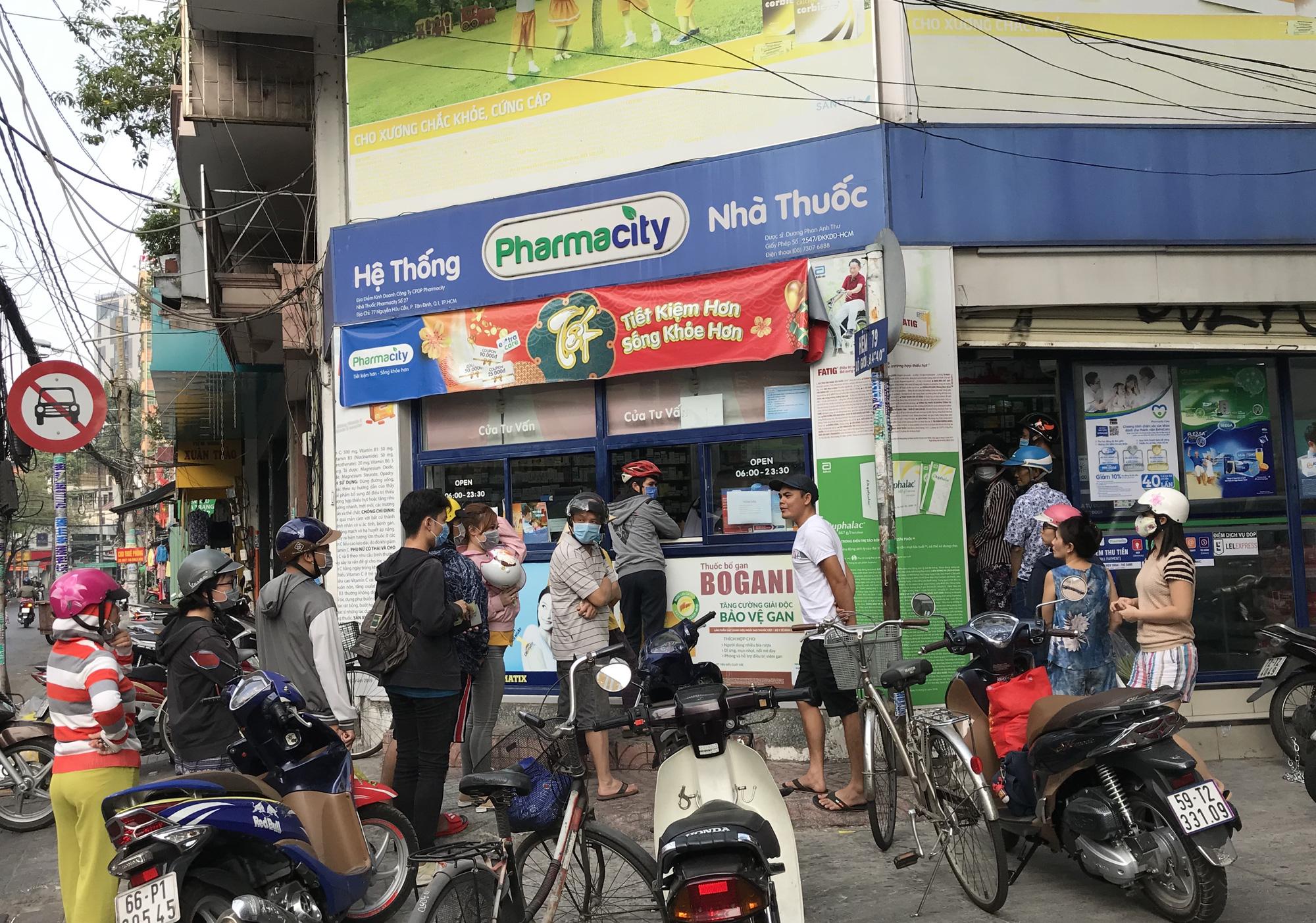 Người Sài Gòn rồng rắn xếp hàng dưới trời nắng để mua khẩu trang 35.000 đồng/hộp - Ảnh 1.