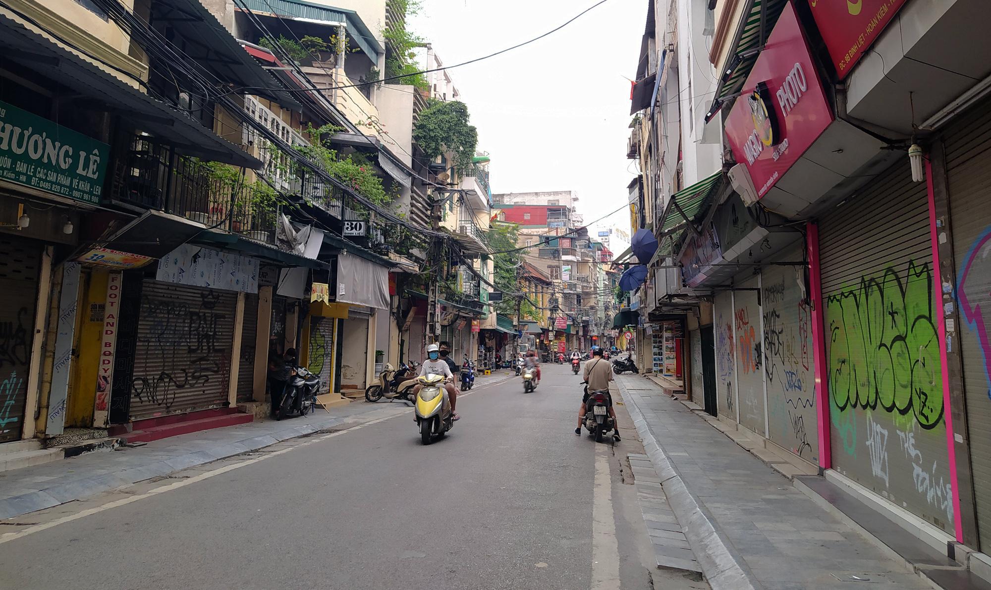 Hà Nội giữa dịch Covid-19: Người dân mặc áo mưa đi mua hàng, nhiều quán cà phê vẫn mở cửa - Ảnh 2.