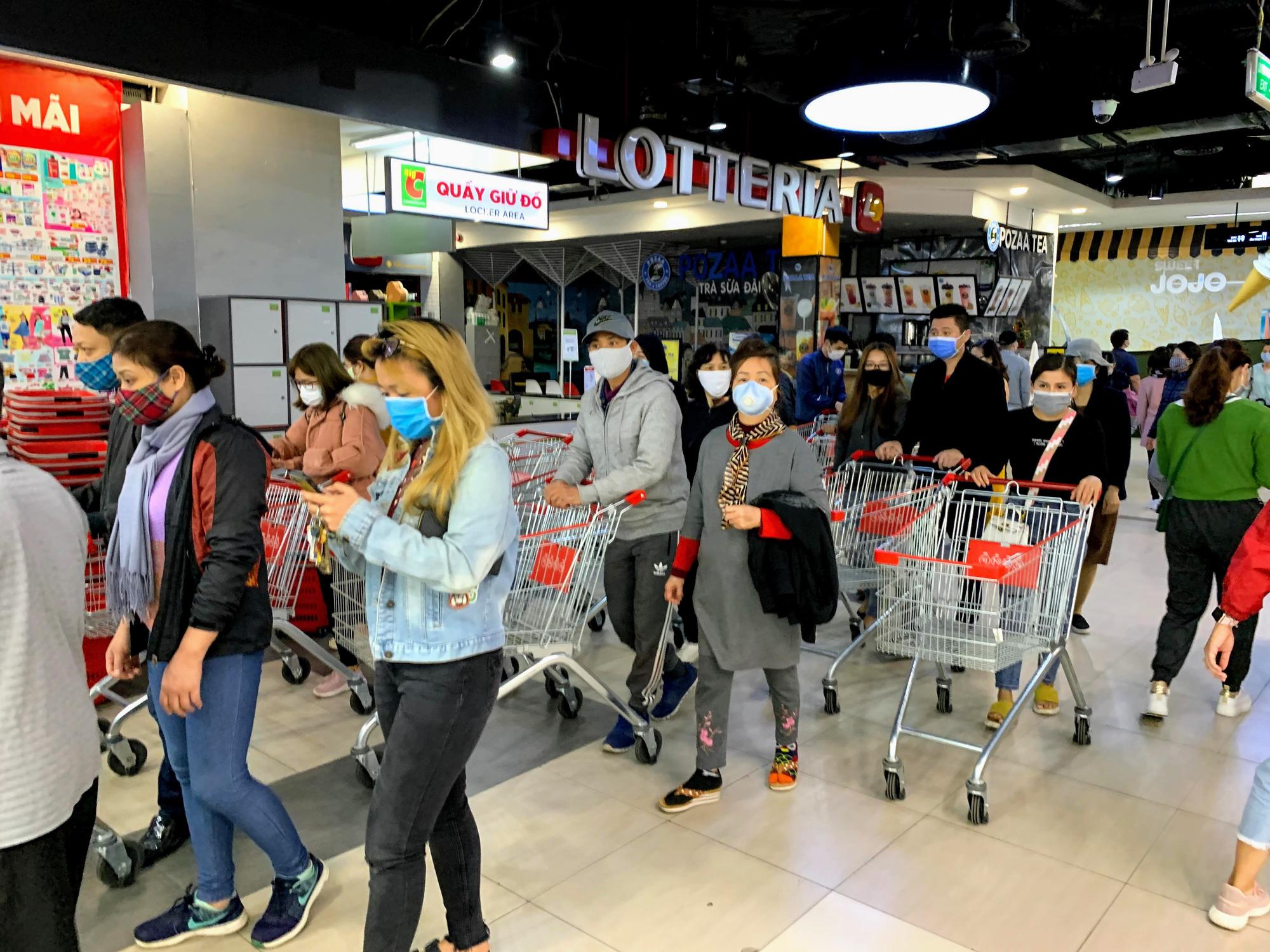 Người Hà Nội kéo đi mua hàng chuẩn bị cho những ngày cách li, nhân viên siêu thị làm việc mỏi tay vẫn không xuể - Ảnh 1.