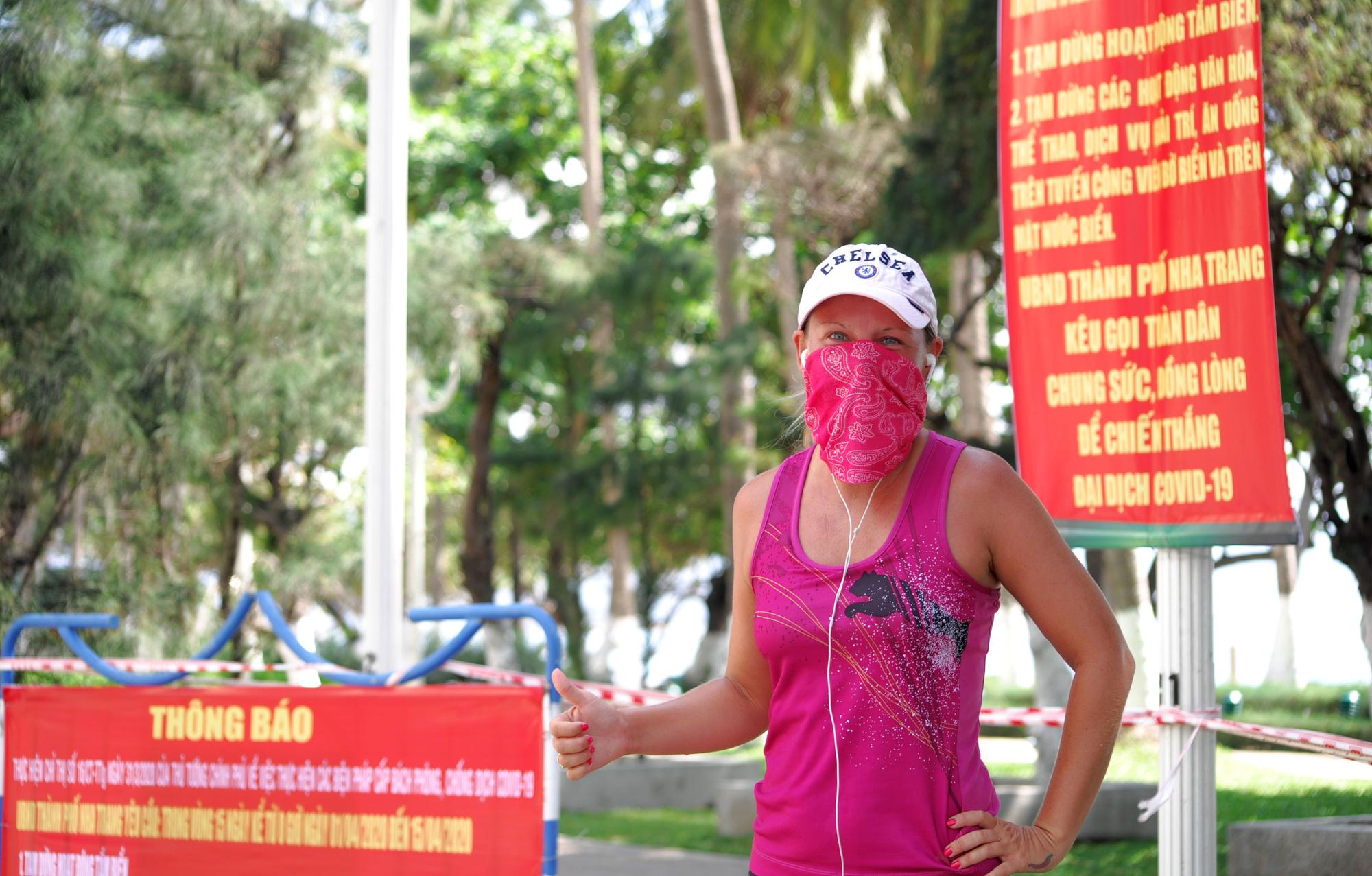 Du khách đeo khẩu trang tập luyện thể thao khi Nha Trang tạm ngừng tắm biển và đóng cửa các điểm vui chơi - Ảnh 12.