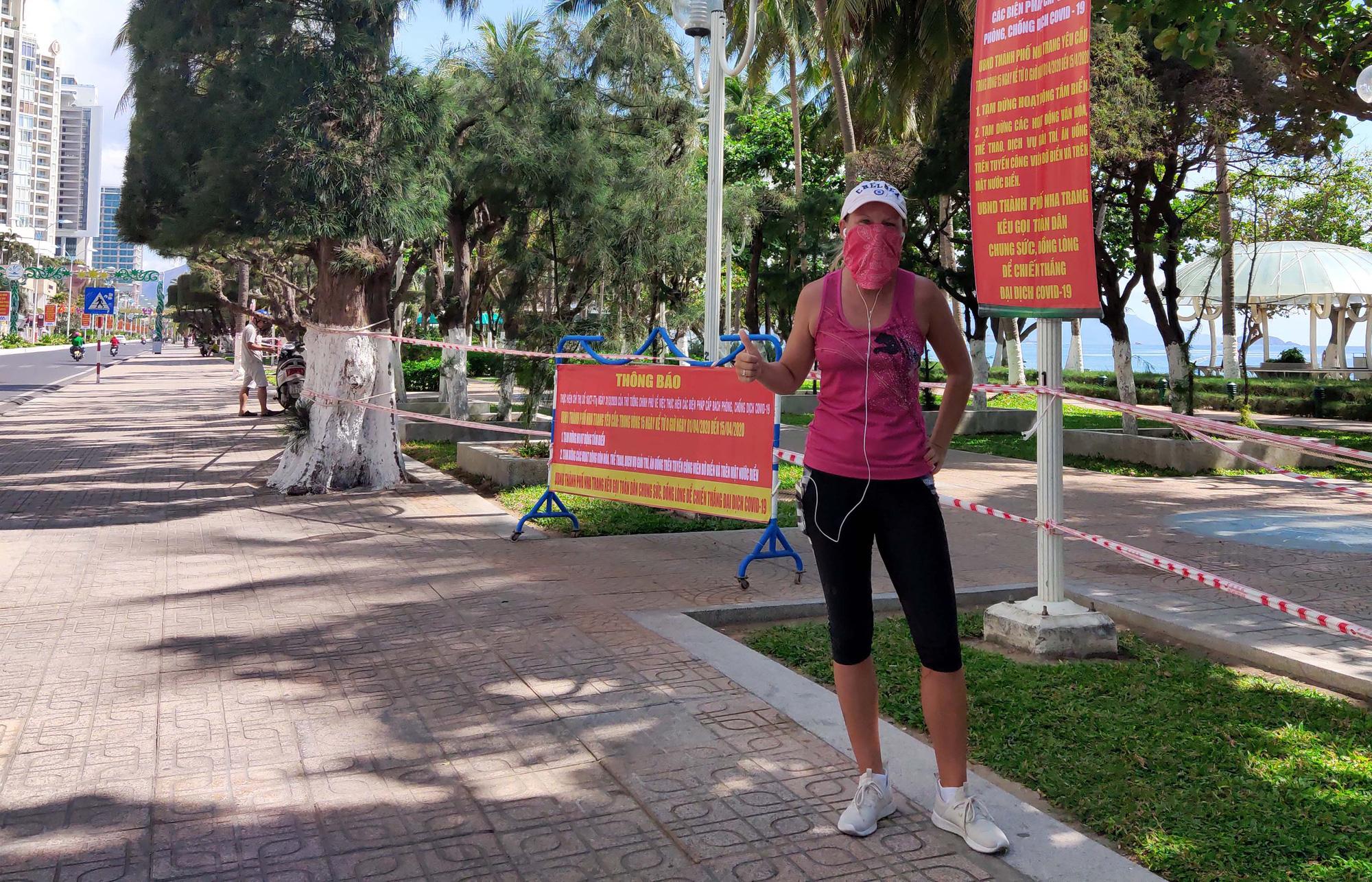 Du khách đeo khẩu trang tập luyện thể thao khi Nha Trang tạm ngừng tắm biển và đóng cửa các điểm vui chơi - Ảnh 4.